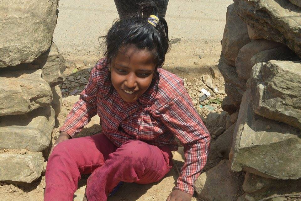 A blind girl sitting on the rubble