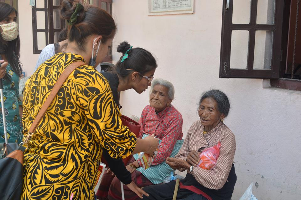 Sristi giving food to old ladies