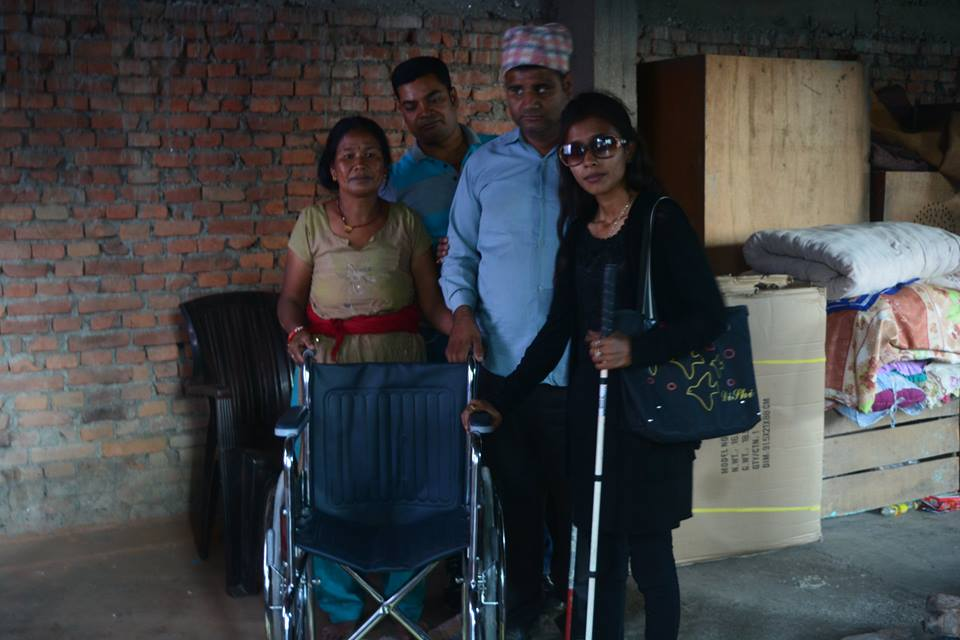 Sristi standing with a wheel chair with member of Blind Rocks and a lady