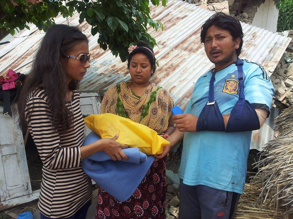 Sristi holding tent and a sac of rice and giving to a person who has broken his arm