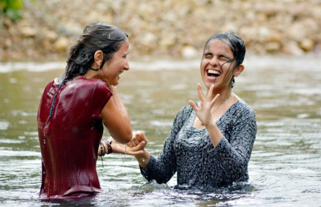 Two blind girls having fun dipping in the river
