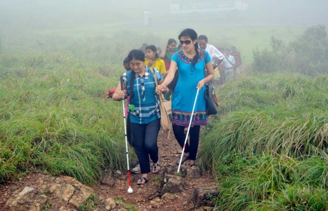 Blind Girls walking between the grass field with white cane