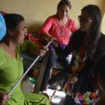 Sristi handing over a white cane to a blind women
