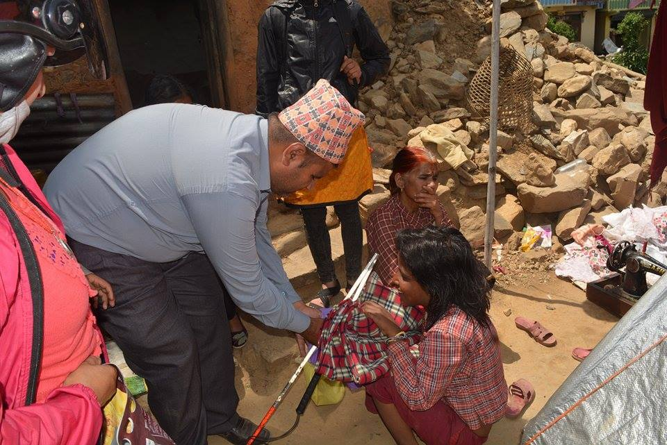 Blind Rock member is handing over clothes and a white cane to a blind women
